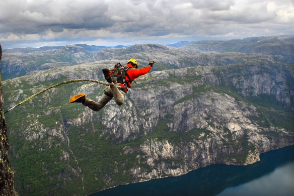 Man jumping off a cliff with a rope.